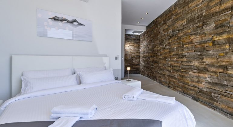 Seafront double bedroom with large stonewall leading to a wellness shower