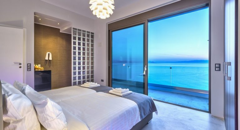 Twin bedroom with seaviews and wellness shower split from the room by a glassbrick wall